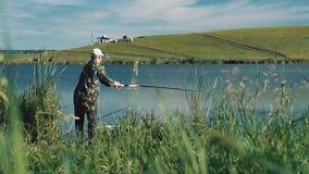 Il pescatore mette una linea fuori con una canna da pesca stock footage