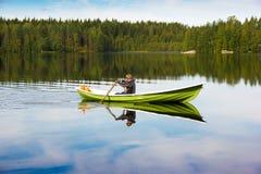 Il pescatore naviga su una barca verde sul lago Immagine Stock