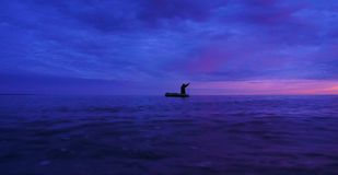 Il pescatore nelle reti da pesca di una barca sul tramonto immagine stock