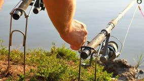 Il pescatore pesca un grande pesce sulla riva del fiume archivi video
