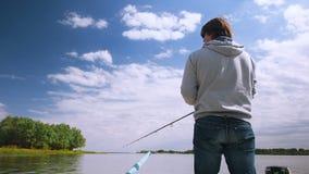Il pescatore pesca un pesce da una barca sul fiume Uomo sulla pesca della barca sulla barretta o sui filatori nel delta di Volga stock footage