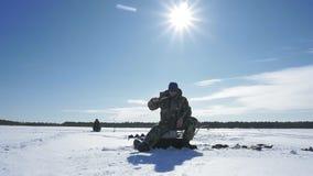 Il pescatore pesca un pesce, sport invernali, hobby dell'inverno archivi video