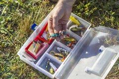 Il pescatore sceglie un'esca di gomma dalla scatola Fotografia Stock Libera da Diritti