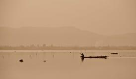 Il pescatore sta navigando per la pesca nel lago Fotografia Stock Libera da Diritti