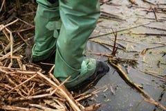Il pescatore sta nell'acqua in stivali impermeabili di gomma per pescare immagini stock