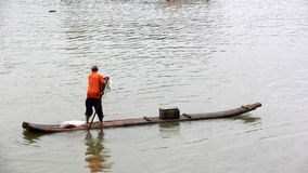 Il pescatore sta remando la zattera di bambù Immagine Stock