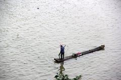 Il pescatore sta remando la zattera di bambù Immagini Stock Libere da Diritti