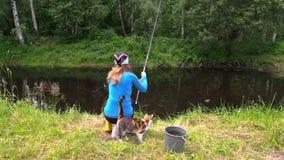 Il pesce biondo della donna sulla riva dello stagno e l'animale domestico sveglio del gatto aspettano il fermo stock footage