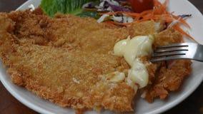 Il pesce del carrello fritto pastella ha avvolto la bistecca del pane con insalata che pugnala dalla forcella sul piatto video d archivio