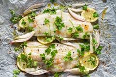 Il pesce fresco, i filetti di merluzzo con prezzemolo, le fette del limone, la cipolla e le spezie hanno preparato per cuocere su fotografia stock libera da diritti