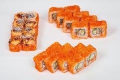 Il pesce giapponese del ristorante dell'alimento dei rotoli di sushi dipende un fondo bianco Immagini Stock
