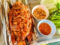 Il pesce rosso di talapia ha grigliato con l'erba in foglio di alluminio che aspetta Fotografie Stock