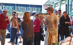 Il pescivendolo sostiene un grande salmone per i turisti Fotografie Stock