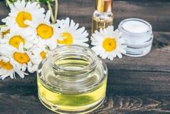 Il petrolio essenziale e la crema cosmetica sono su una tavola di legno vicino ai fiori della camomilla bianca immagine stock libera da diritti