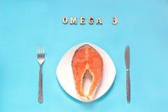 Il pezzo della bistecca di rosso ha marinato il pesce sul piatto, sul coltello e sulla forcella bianchi fotografie stock