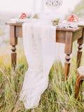 Il pezzo della copertura di tavola del pizzo che si trova sulla tavola e sull'erba fotografie stock libere da diritti