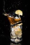 Il pezzo di caduta di ghiaccio in un vetro di alta qualità di whiskey con molti spruzza Immagine Stock Libera da Diritti