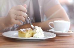 Il pezzo di dolce dolce cremoso ha tagliato una mano del ` s dell'uomo con una forcella fotografia stock