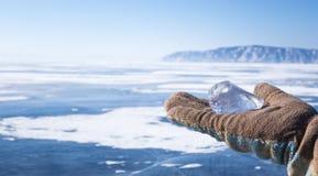Il pezzo di ghiaccio che mette sulla palma si è vestito in guanto Ghiaccio puro di baikal sotto cielo blu Immagini Stock