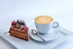 Il pezzo di torta del cioccolato con le bacche selvatiche è servito con la tazza del cappucino Fotografia Stock