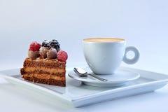 Il pezzo di torta del cioccolato con le bacche selvatiche è servito con la tazza del capucino eccellente Immagine Stock