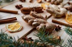 Il pezzo di zenzero sui precedenti di legno con gli ingredienti tradizionali delle spezie per il forno o il vin brulé di Natale h Fotografie Stock
