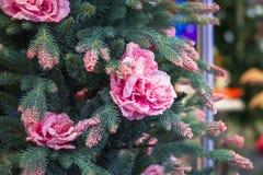 Il più nuovo albero di Natale artificiale moderno con i fiori ed i rami innevati rosa Immagine Stock