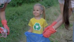 Il pianeta di risparmio, giovane famiglia con la ragazza sveglia felice del bambino in guanti di gomma raccoglie i rifiuti nella  archivi video