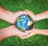 Il pianeta Terra della tenuta dell'uomo con il bambino Fotografie Stock Libere da Diritti