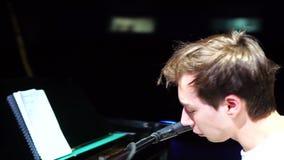 Il pianista barbuto moderno franco canta una canzone ed emozionalmente gioca il piano video d archivio