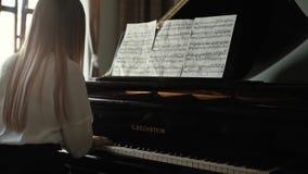Il pianista della ragazza gioca la musica classica calma su una fine del pianoforte a coda su video d archivio