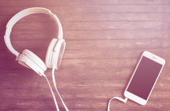 Il piano bianco delle cuffie e del telefono mette sulla tavola di legno La luce rosa calda ha tonificato la foto Immagini Stock Libere da Diritti