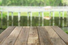 Il piano d'appoggio di legno sulla natura verde ha offuscato gli ambiti di provenienza Fotografia Stock Libera da Diritti