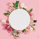 Il piano decorativo pone la composizione con i prodotti di bellezza, i cosmetici ed i fiori Disposizione piana, vista superiore s fotografia stock libera da diritti