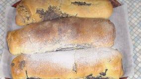 Il piano del primo piano, polvere dello zucchero riempie sui rotoli al forno di materiale da otturazione del papavero video d archivio