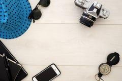Il piano di concetto di viaggio pone al di sopra su legno bianco, con i vetri di sole e della macchina fotografica Immagini Stock