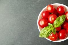 Il piano di Minimalistic pone la composizione dei pomodori ciliegia rossi brillanti che riflettono la luce in ciotola bianca sul  immagine stock libera da diritti