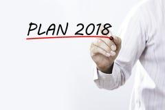 Il piano 2018 di scrittura della mano dell'uomo d'affari con l'indicatore rosso sopra transparen Immagine Stock