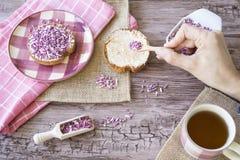 Il piano pone con fetta biscottata, la porpora rosa dolce spruzza e tazza di tè Contro fondo di legno fotografie stock