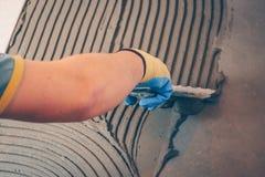 Il piastrellista applica la colla sul pavimento fotografia stock