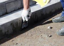 il piastrellista elabora la superficie per la stenditura delle mattonelle di pietra sui punti nella riparazione dell'edificio per Fotografie Stock
