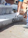 il piastrellista elabora la superficie per la stenditura delle mattonelle di pietra sui punti nella riparazione dell'edificio per Fotografie Stock Libere da Diritti