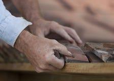 Il piastrellista misura le mattonelle del bordo sul bordo del tetto di mattonelle dell'argilla Immagini Stock