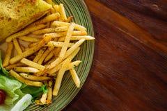 Il piatto è servito con le patate fritte, un involucro e un'insalata Fotografia Stock Libera da Diritti