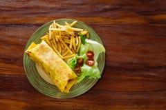 Il piatto è servito con un involucro, le verdure e le patate fritte Fotografie Stock Libere da Diritti