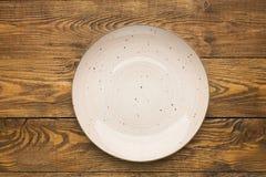 Il piatto ceramico rosa vuoto sopra woden la tavola fotografie stock