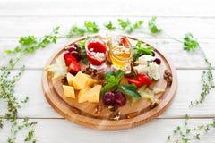 Il piatto con vino fa un spuntino nel telaio di erbe su bianco Fotografia Stock Libera da Diritti