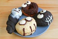 Il piatto dei mostri e dei fantasmi di Halloween ha modellato le ciambelle servite sulla Tabella di legno Fotografie Stock