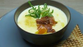 Il piatto del ristorante, minestra crema kitsch decorata con un ramoscello della rucola, bacon tostato con pane tostato, il capo  video d archivio