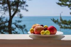 Il piatto della frutta con le pesche mature, le ciliege succose e le prugne sulla spiaggia riposano su un balcone di legno sui pr Immagine Stock